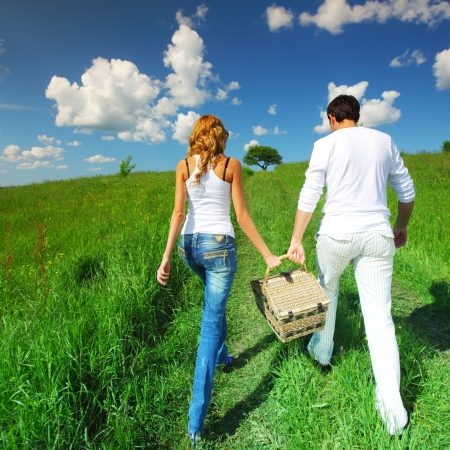 man and woman walk on picnic in green grass photo