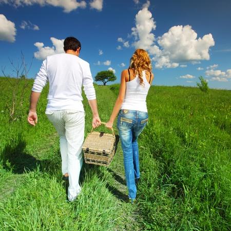 pique nique en famille: homme et femme marchent sur pique-nique en herbe verte