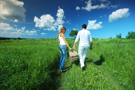 relationship love: man and woman walk on picnic in green grass