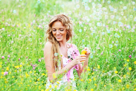 Blonde starts soap bubbles in a green field Stock Photo - 8752964