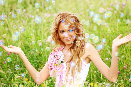 Blonde starts soap bubbles in a green field Stock Photo
