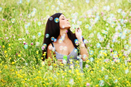 hands behind head:  happy woman smile in green grass soap bubbles around