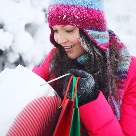 christmas pink: winter girl with gift bags on snow background