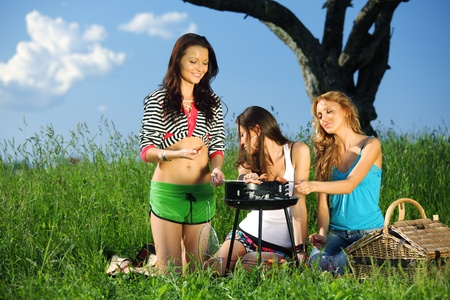 barbecue party: girls burn sausages on barbecue Stock Photo