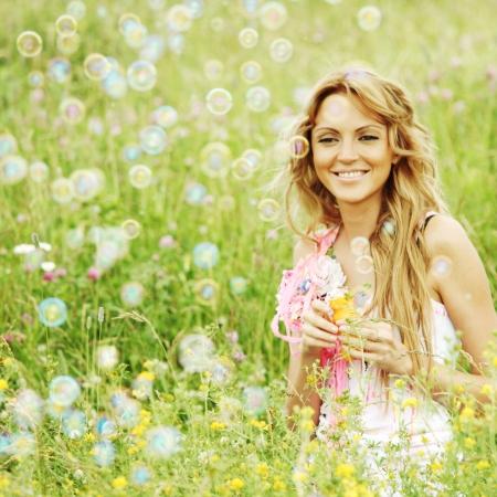 Blonde starts soap bubbles in a green field photo