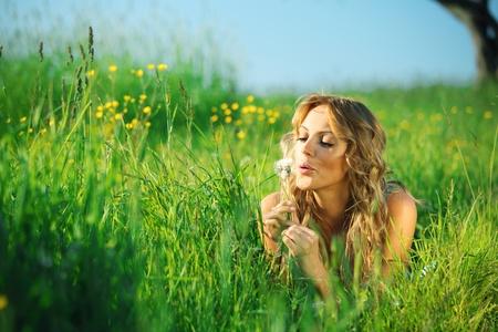girl blow on dandelion on green field photo