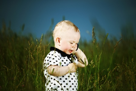 little boy in green grass call by phone photo