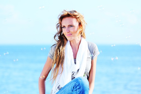 happy blond hair woman sea on background photo