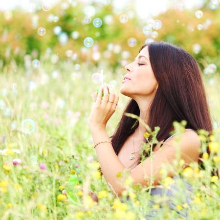 happy woman smile in green grass soap bubbles around Stock Photo - 8826707