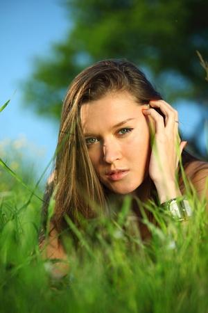 happy woman lay on green grass under tree photo