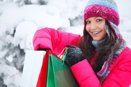 winter girl with gift bags on snow background Stock Photo - 8826566