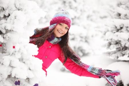 ropa de invierno: chica de invierno detrás de árbol de nieve  Foto de archivo