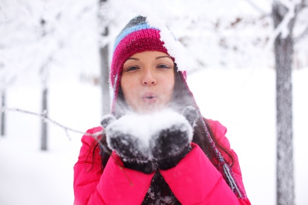 winter girl blow on snow in hands Stock Photo - 8826511
