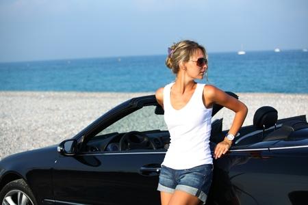 ragazze bionde:  donna vicino mare auto sullo sfondo Archivio Fotografico