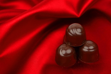 chocolate candy on red satin background photo