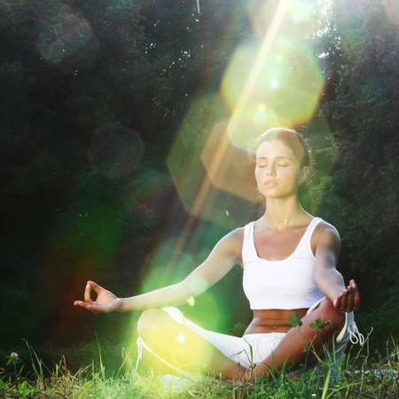 health and beauty: yoga woman on green grass lotus pose in sunrise light