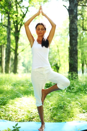 yoga woman on green grass in forest Stock Photo - 8917358
