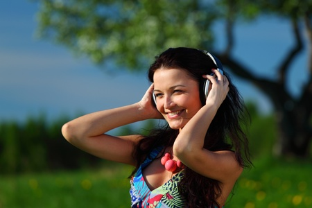 Young woman with headphones listening to music on field Stock Photo - 8917337