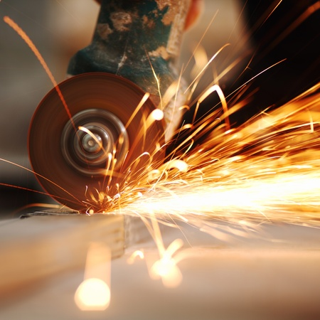 electric saw: metal sawing close up sparks spray