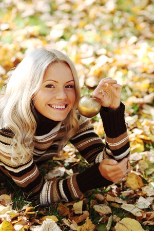 woman with golden apple in autumn park photo