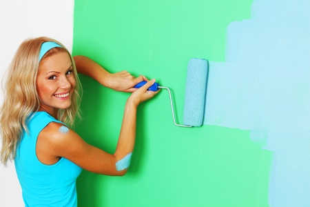woman paints the wall roller photo