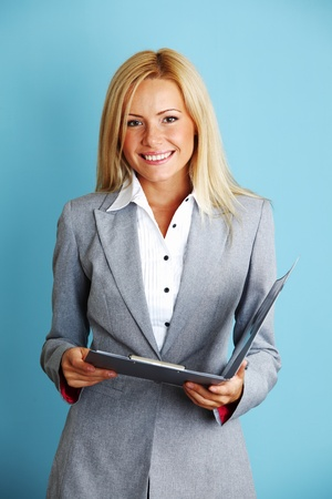 business woman hold a folder of papers on a blue background photo
