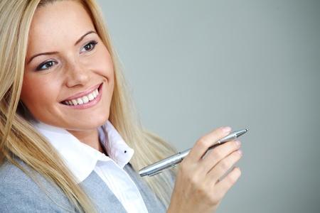 bussines: zakenvrouw op grijze achtergrond pen in handen