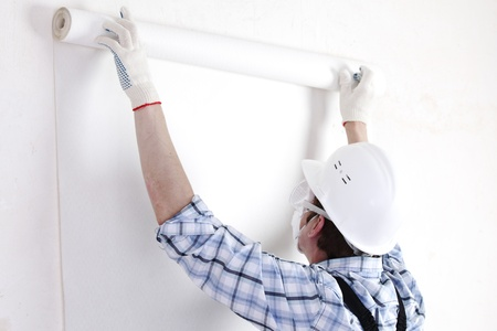 house renovation: worker attaching wallpaper to wall