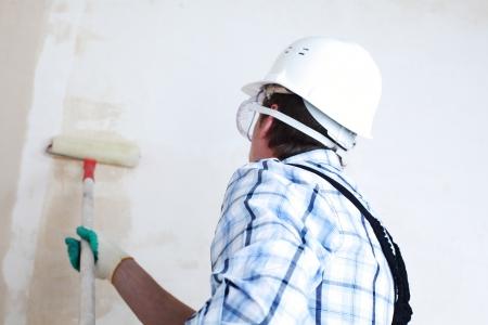 pintora: trabajador pasa rodillos de anclaje en la pared