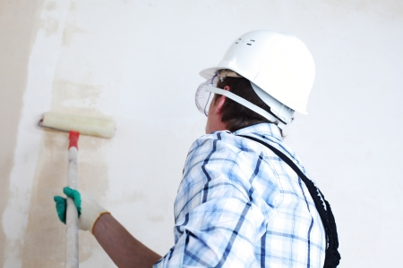 house painter: worker spends anchor roller on the wall