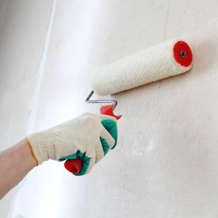 pintor de casas: trabajador pasa rodillos de anclaje en la pared