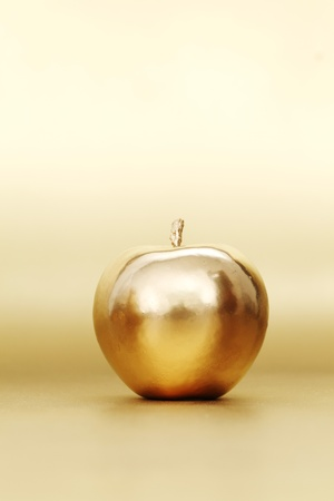 gold apple on gold background Stock Photo - 9121259