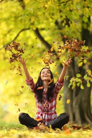 woman drop up leaves in autumn park Stock Photo - 9130899