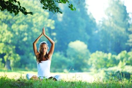 ライフスタイル: ロータスの緑の草にヨガ女性をポーズします。