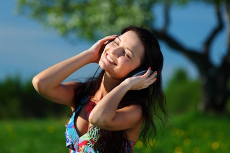 Young woman with headphones listening to music on field Stock Photo - 9121312