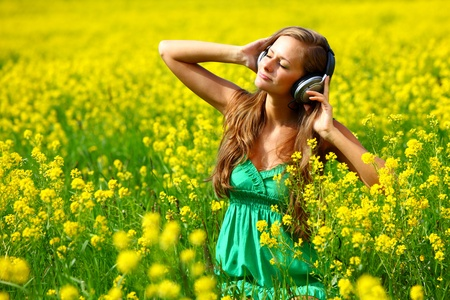 Young woman with headphones listening to music on oilseed flowering field photo