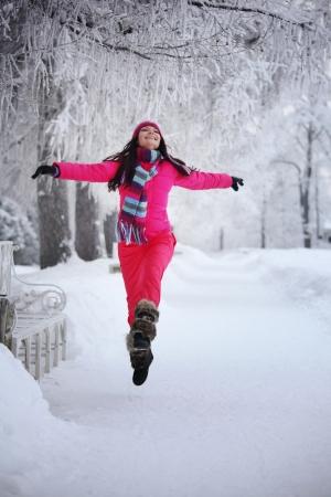 neige qui tombe: femme situ? dans le parc d'hiver tr?s heureux