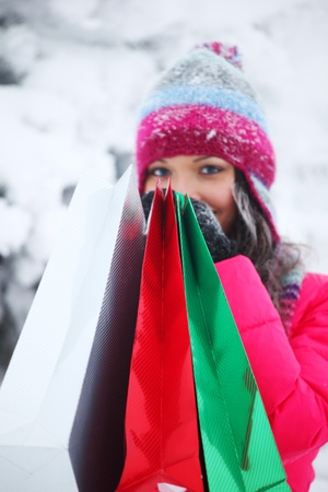 winter girl with gift bags on snow background photo