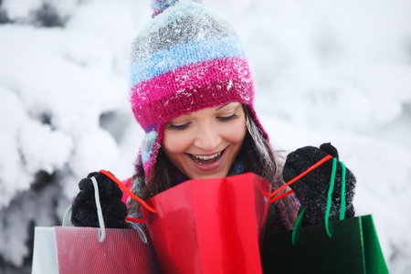 winter sales: winter girl with gift bags on snow background