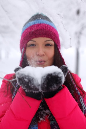 winter girl blow on snow in hands photo