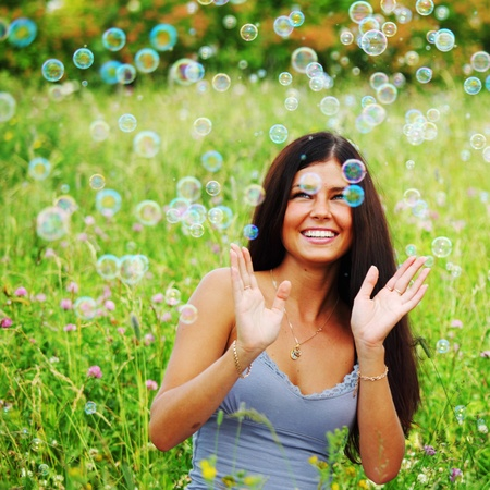 girlfriends on green grass field in soap bubbles photo