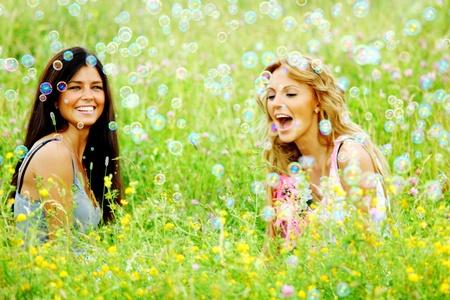 girlfriends on green grass field in soap bubbles photo