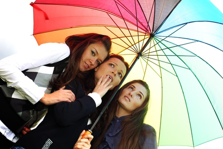 girlfriends stay under colourful umbrella  photo