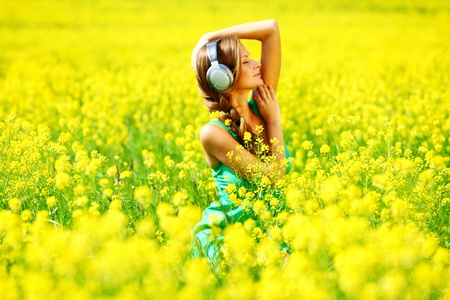 oilseed:  Young woman with headphones listening to music on oilseed flowering field