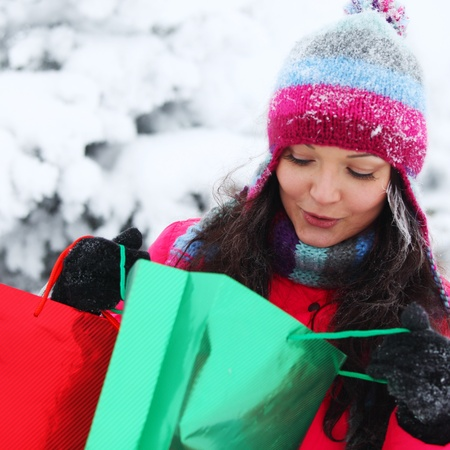christmas girl: winter girl with gift bags on snow background