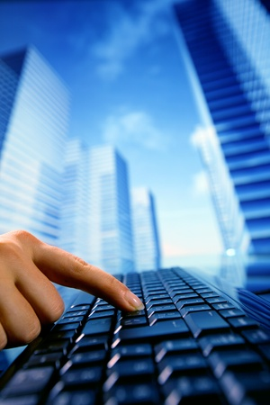 corporation: reseller work on keyboard skyscrapers on background Stock Photo