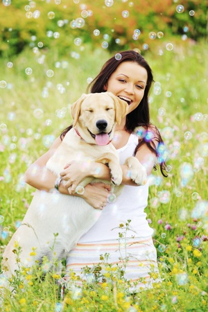 woman and she lablador dog in green grass photo