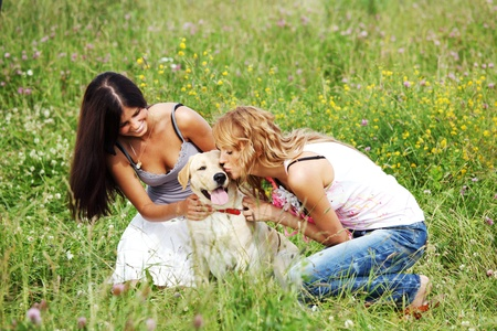girlfriends and dog in green grass field photo