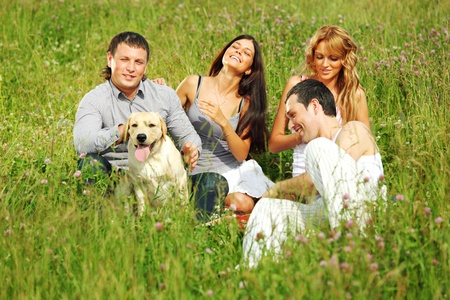 friends and dog in green grass field photo