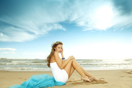 woman laying on sand sea on background photo